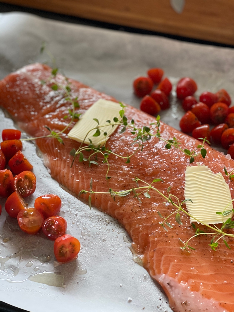 Side of salmon, prior to going into the oven. Lumps of butter, fresh thyme and cherry tomatoes are also visible on the baking tray.