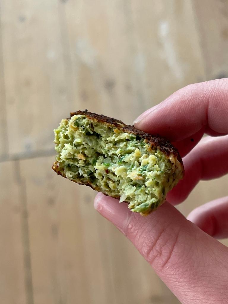 En grøn frikadelle på kyllingekød, hvor der er taget en bid af