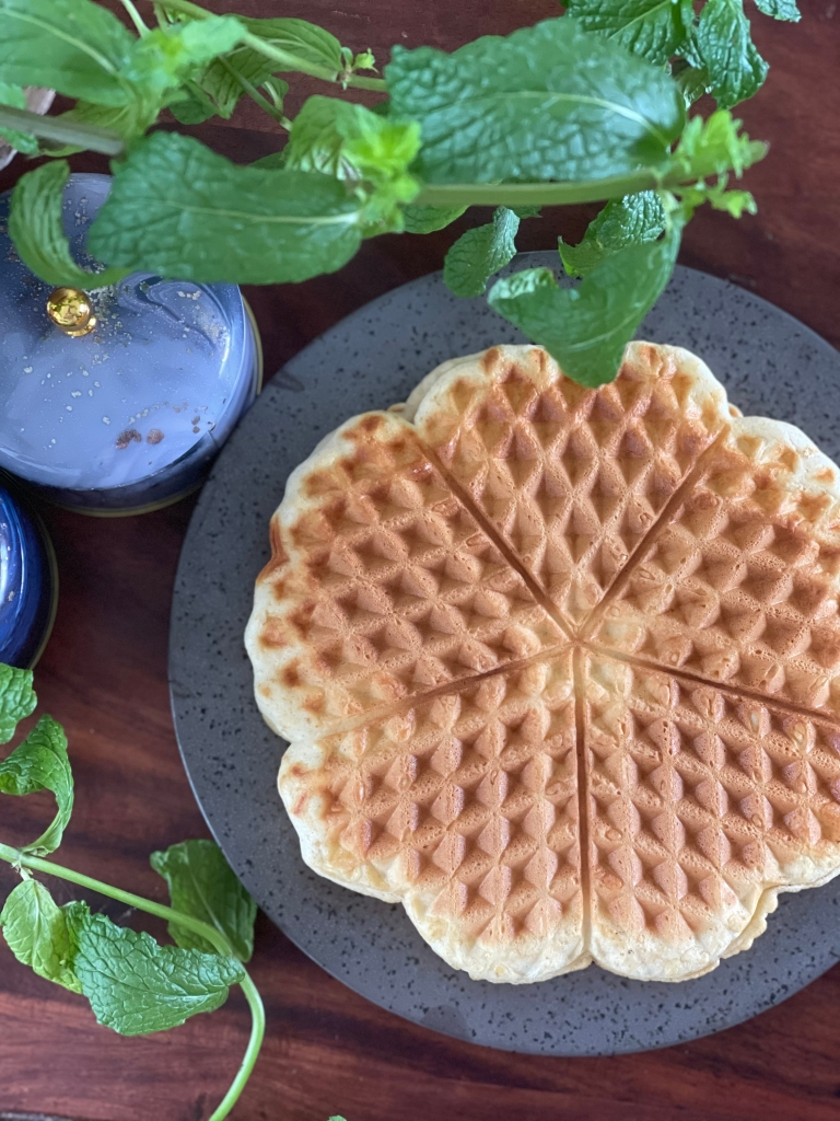 Flatlay of protein waffles, accompanied by a sprig of mint and marbled containers. On a dark wooden desk.