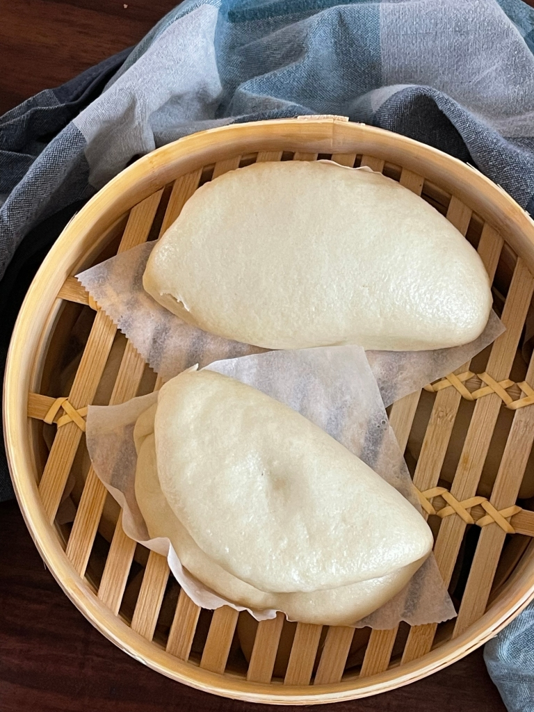 Two bao buns are seen from above, within a bamboo steam cooker. A checkered blue kitchen towel is around the bamboo steamer.