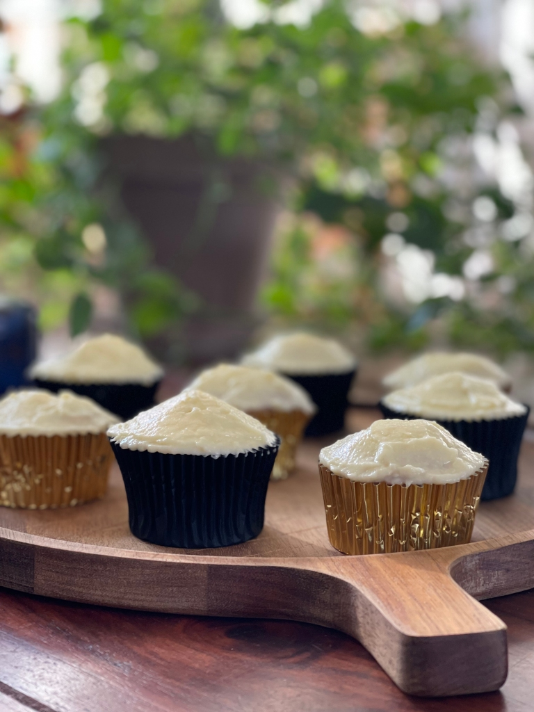 8 cupcakes, alternating in gold and black colors, stand on a wooden board with a lush, green background. It's serene.